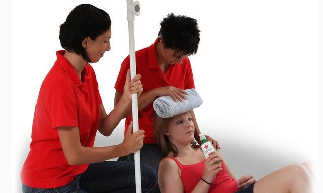 Jugendliche liegt nach Sonnenstich mit leicht erhöhtem Oberkörper und trinkt Wasser, Helfer spenden Schatten und halten kühlen Umschlag auf die Stirn,