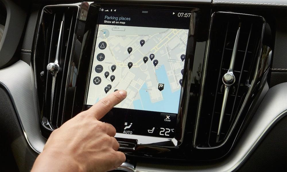 Mann tippt mit Finger auf Volvo XC40 Navigationssystem